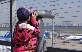 An AvGeek-in-training uses a telescope on HND T2's observation deck. See the cables?