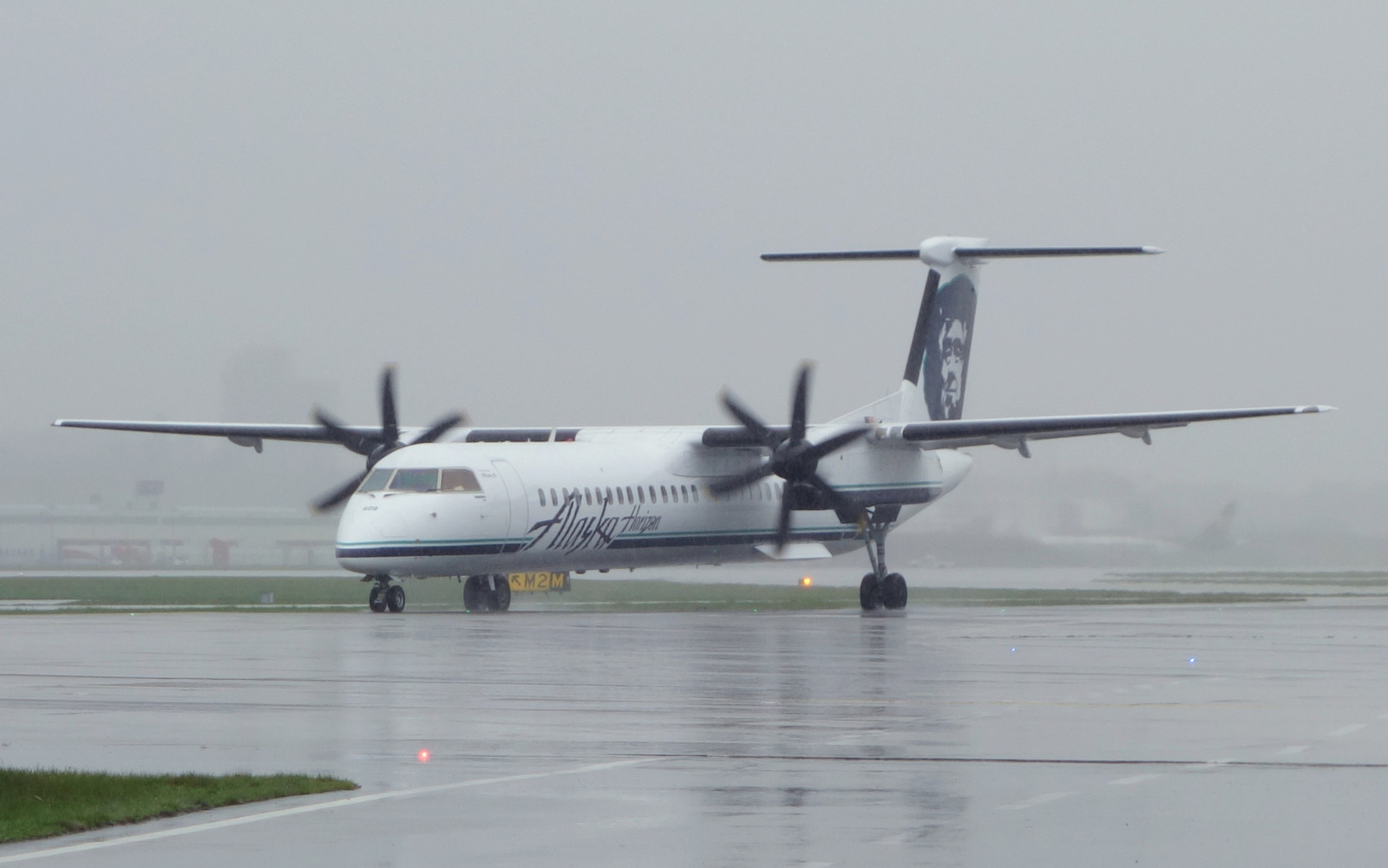 Horizon Airlines Q400 taxies in the rain at YVR