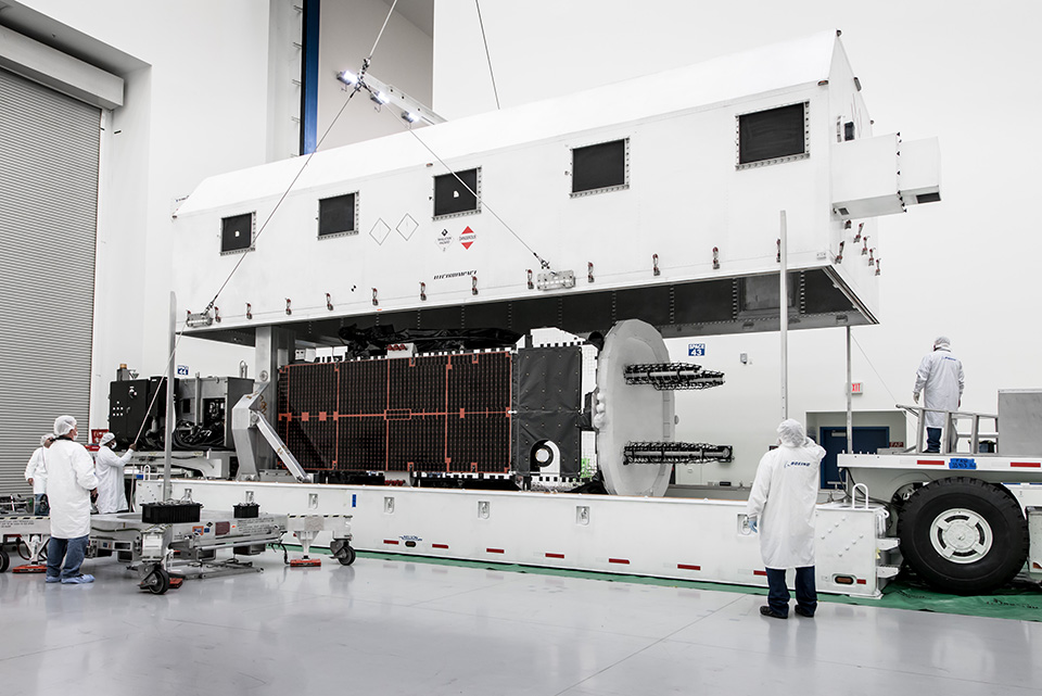 A communications satellite is loaded into its shipping container. Photo: Boeing