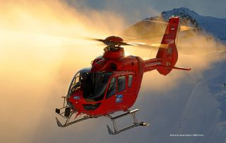 An H135 belonging to Heli-Austria flies in front of a peak in the Austrian Alps. Photo: Anthony Pecchi