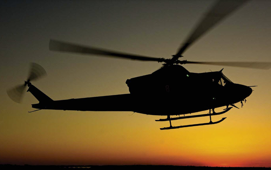 A Bell 412 flies at sunset with the distinctive outline of the BLR FastFin System in its tail.. Photo: Mike Reyno | Vertical Magazine